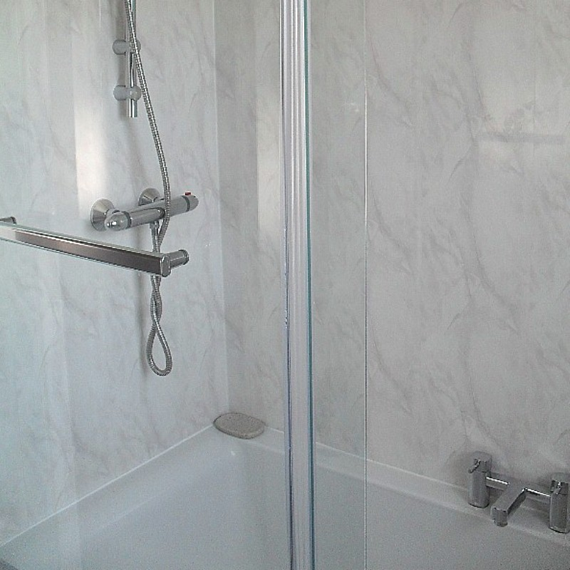 A shower bath fitted with Vicenza bathroom cladding